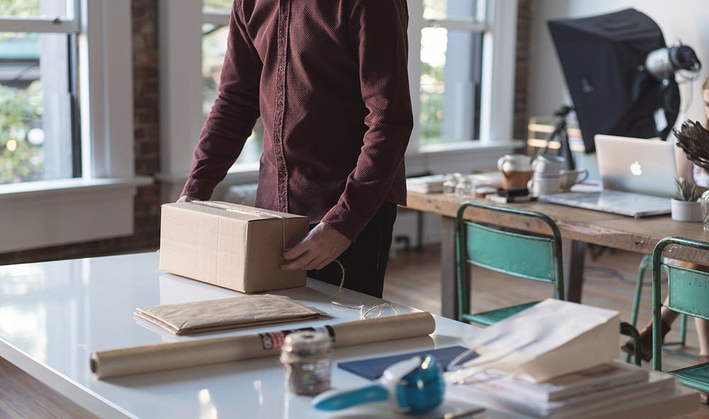 Man in commercial setting wrapping a package to ship